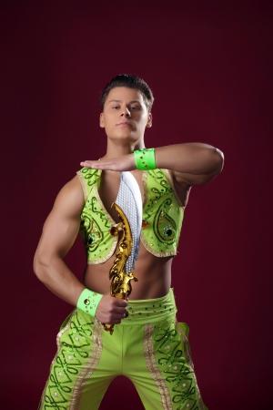 broadsword: Portrait of dancer posing in oriental costume, on red background