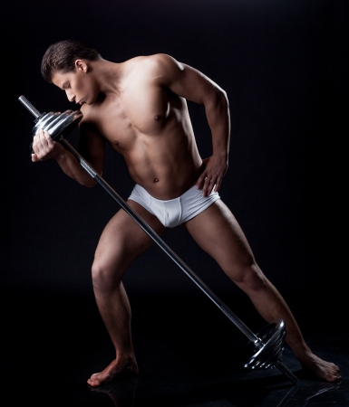 brawny: Brawny young man posing kissing barbell, isolated on black