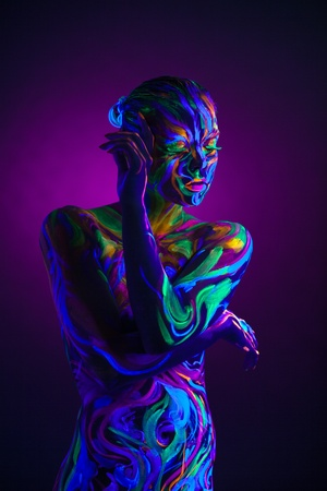 Sexual dancer posing with UV pattern on body, close-up