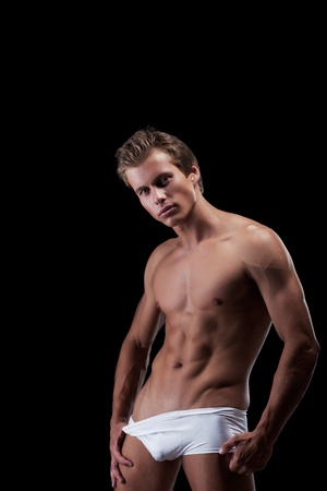 Seductive muscular man posing looking at camera, isolated on black photo