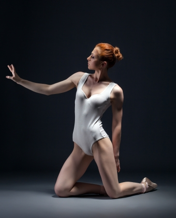 Image of skinny young ballerina posing in studio, close-up photo
