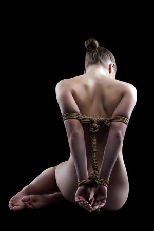 ragazza nuda: Ragazza nuda legata con la corda in posa nuovo alla macchina fotografica, isolato su fondo nero