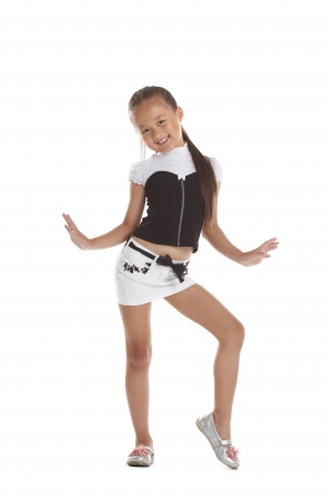 Freundliches kleines Mädchen posiert im modischen Kostüm, isoliert auf weiß