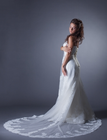 Slender brunette posing in stylish wedding dress, on gray background photo