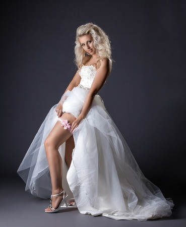 Image of sensual young bride shows garter on leg, close-up photo