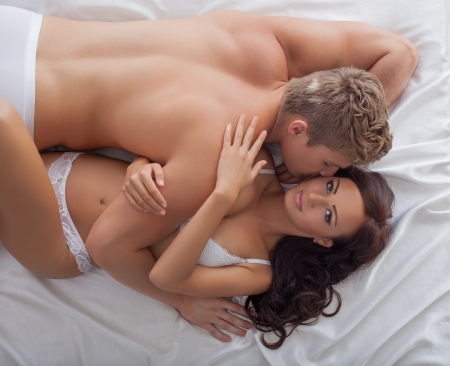 Image of passionate lovers hugging in bed, close-up photo