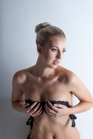 Portrait of graceful slim blonde posing in black bra, close-up photo