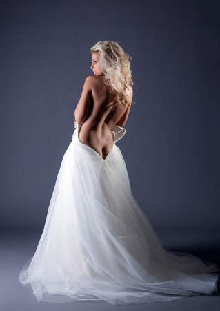 sexy nude blonde: Seductive topless bride posing back to camera, on gray background