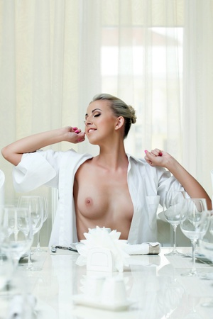 Sexy smiling topless girl stretches while sitting at table, close-up Stock Photo