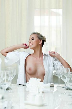 topless: Sexy sourire fille topless s'étend alors qu'il était assis à la table, close-up