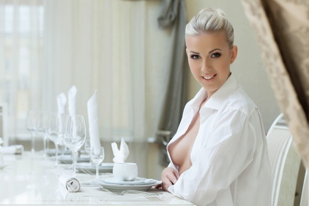 Seductively smiling woman sits in restaurant, close-up photo