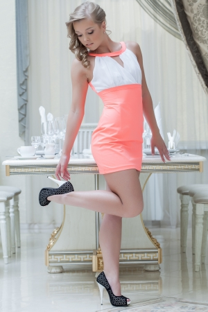 Pretty smiling model posing in elegant pink dress, close-up