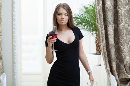 sexy black dress: Portrait of sexy girl in tight black dress posing in hotel Stock Photo