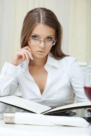 seductive women: Portrait of pensive business woman in glasses posing with folder