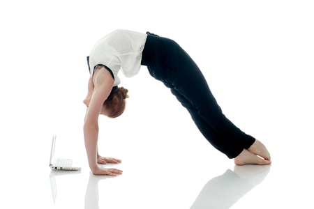 Business lady doing gymnastics and posing with PC, isolated on white background photo