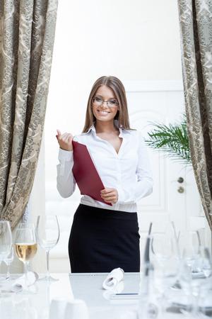 blusa: Imagen de amable anfitriona posando en el restaurante, de cerca Foto de archivo
