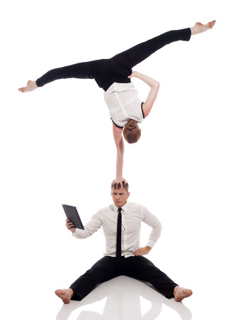 Businessmen-acrobats posing with laptop in studio. Concept of busyness. photo
