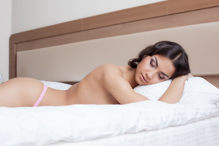 Image of sexy brunette lying on bed, close-up photo