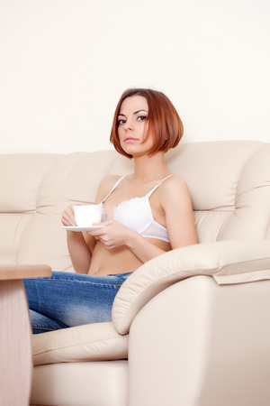 Portrait of charming girl with short hair drinks tea, close-up photo
