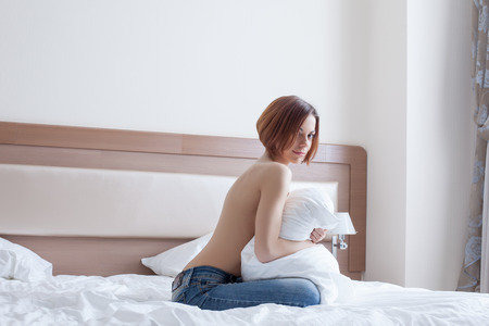 Smiling topless girl posing with pillow on bed, close-up photo
