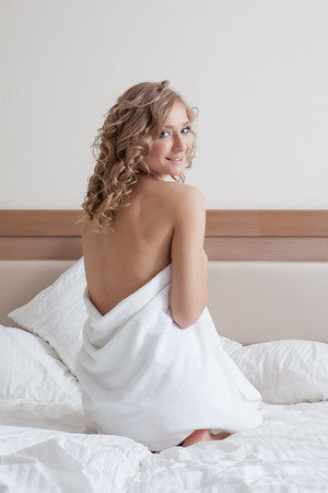 Attractive young girl in towel posing on bed, close-up photo