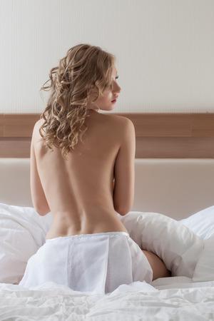 Sensual topless model posing back to camera, close-up photo
