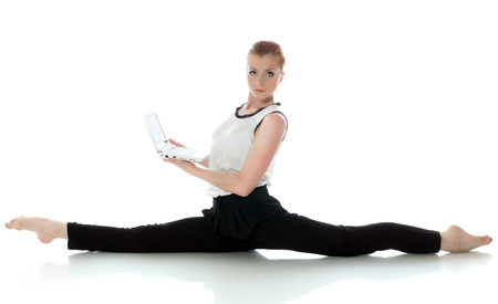 Serious young gymnast posing with laptop. Concept of multitasking. photo