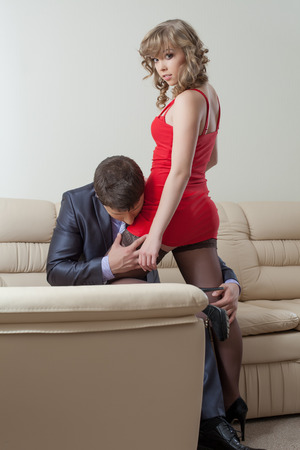 erotic dress: Image of businessman kissing pretty girl in erotic dress Stock Photo
