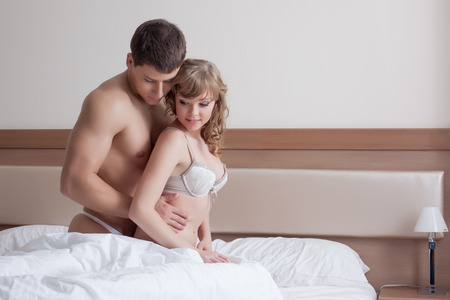 Couple of sensual young lovers posing in bed, close-up photo