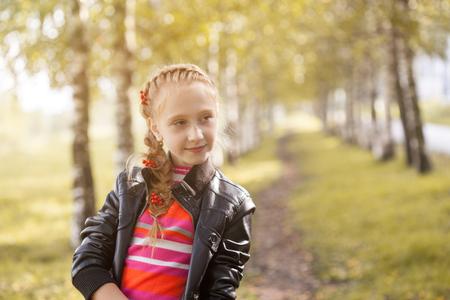 charming girl: Charming little girl posing in autumn garden, close-up Stock Photo