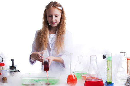 reagents: Curious schoolgirl mixes reagents in studio, isolated on white
