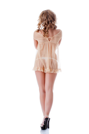 Curly fille mince posant en d�shabill� �rotique beige, isol� sur blanc photo