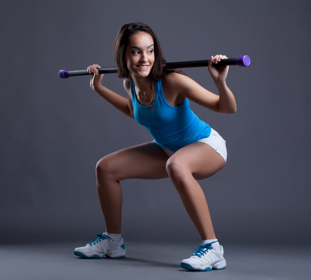 crouches: Smiling sporty woman crouches with fitbar, on gray background