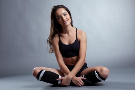 gaiters: Relaxed smiling brunette posing in sportswear, on gray background