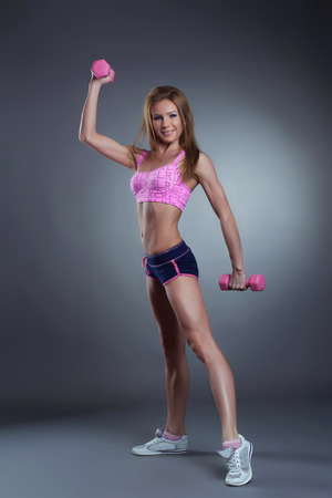slim girl: Image of pretty strong woman exercising with dumbbells