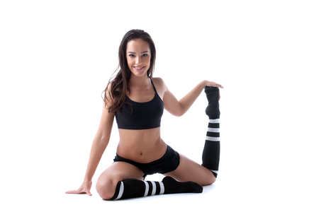 gaiters: Pretty merry brunette doing stretching in studio, isolated on white Stock Photo