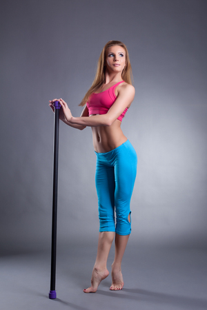 young girl barefoot: Image of pretty young woman standing on tiptoe with fitbar