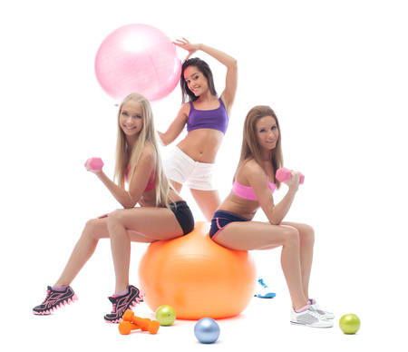 posing: Smiling young sporty girls posing with fitness items Stock Photo