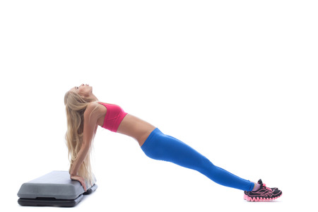 sexy blonde girl: Long-haired slim woman exercising on stepper, isolated over white background Stock Photo