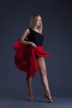 donna che balla: Pretty sensual woman dancing with red cloth in studio Archivio Fotografico