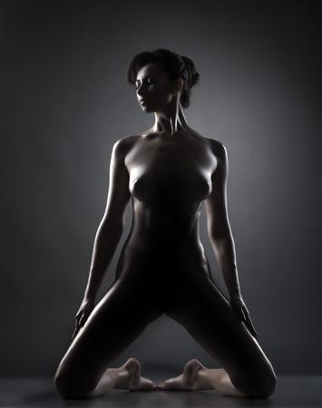 naked silhouette: Studio shot of seductive naked oiled model, on gray backdrop