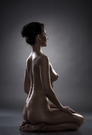 sexy women naked: Profile of sensual oiled young model sits in studio, close-up