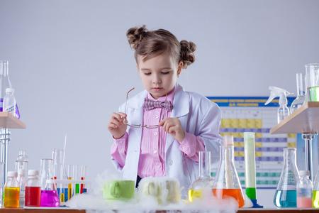 evaporacion: Concentrada de la muchacha mira a través de sus gafas en la evaporación del reactivo