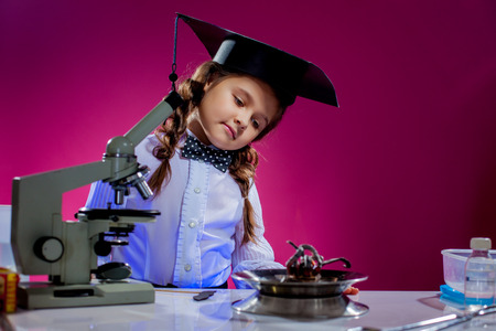 discovery: Portrait of curious little girl posing in science lab