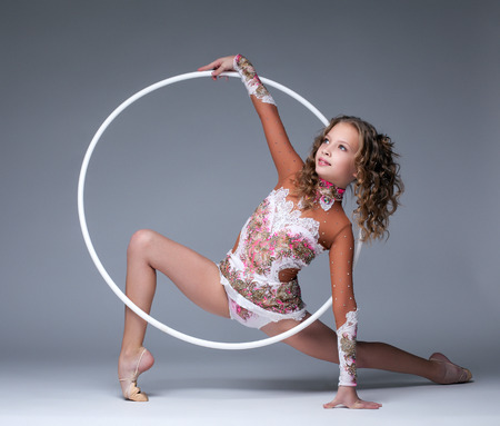 young gymnast: Image of elegant young gymnast dancing with hoop in studio Stock Photo