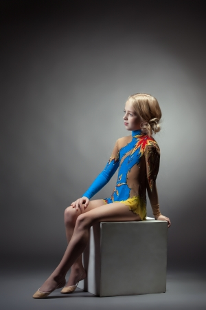 Image of thoughtful gymnast posing in colorful leotard photo