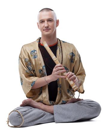 guru: Yoga guru playing flute, isolated on white background