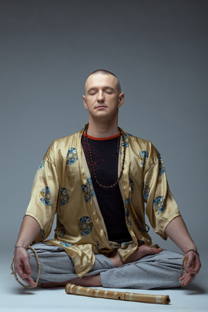 meditates: Image of yoga guru meditates in studio, on gray background