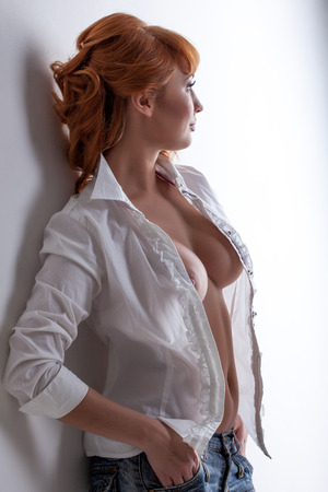 Hot red-haired woman posing in unbuttoned blouse, close-up photo