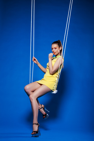 Image of flirtatious disco model posing on swing photo